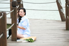 Chinese young beautiful woman sit on bridge see lake in park Royalty Free Stock Photos