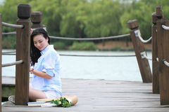 Chinese young beautiful woman sit on bridge see lake in park Stock Image