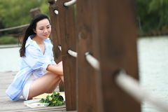 Chinese young beautiful woman sit on bridge see lake in park Royalty Free Stock Image
