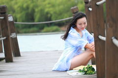Chinese young beautiful woman sit on bridge see lake in park Royalty Free Stock Photography