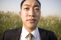 Chinese young man. In suit in nature ,not happy Stock Photo