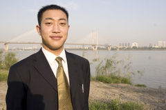 Chinese young man. In suit.Taken near  the Yangtse River ,a bridge at background Royalty Free Stock Photos