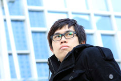 Chinese young man. Image of pensive guy looking aside on the background of modern office building Royalty Free Stock Photos