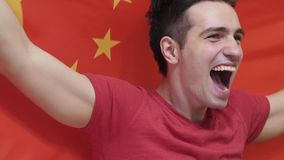 Chinese Young Man Celebrating while holding the Chinese Flag in Slow Motion. High quality royalty free stock image