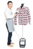 Chinese young man ironing his clothes. Young man ironing his clothes isolated against white background Royalty Free Stock Image