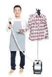 Chinese young man ironing his clothes. Young man ironing his clothes isolated against white background Stock Images