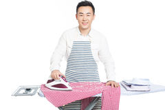 Chinese young man ironing his clothes. Young man ironing his clothes isolated against white background Stock Photo