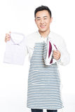 Chinese young man ironing his clothes Royalty Free Stock Photo