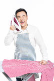 Chinese young man ironing his clothes. Young man ironing his clothes isolated against white background Royalty Free Stock Photography