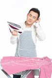 Chinese young man ironing his clothes. Young man ironing his clothes isolated against white background Royalty Free Stock Photo