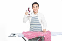 Chinese young man ironing his clothes. Young man ironing his clothes isolated against white background Stock Photography