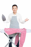 Chinese young man ironing his clothes. Young man ironing his clothes isolated against white background Stock Photos