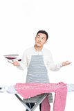 Chinese young man ironing his clothes Royalty Free Stock Photography
