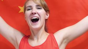 Chinese Young Woman Celebrating while holding the Chinese Flag in Slow Motion. High quality stock images