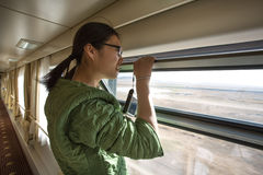 Chinese young woman looking by an open window in train royalty free stock photos