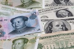 Chinese yuan and American dollars as a background. Chinese yuan and American dollars are laid out as a background stock images