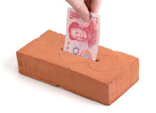 Chinese Yuan deposit into a building brick. Chinese Yuan bank note in a piggy bank or tissue box like brick Stock Images