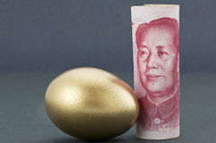 Chinese yuan money with gold egg on tranquil dark background Royalty Free Stock Image