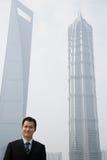 Chinese zakenman dichtbij wolkenkrabbers Royalty-vrije Stock Afbeeldingen