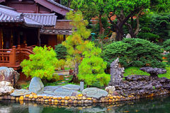 Chinese zen garden view. Pagoda in front of a pond in a beautiful chinese garden surrounded with attractive colors of spring foliage royalty free stock image