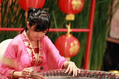 Chinese zither. A Chinese girl in traditional dress is performing the zither of China Stock Photography