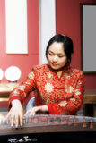 Chinese zither . A Chinese girl in traditional dress is performing the zither of China Royalty Free Stock Photo