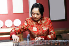 Chinese zither . A Chinese girl in traditional dress is performing the zither of China. The zither is a very famous Chinese folk musical instrument, history is Stock Photo