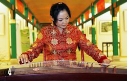 Chinese zither . A Chinese girl in traditional dress is performing the zither of China Stock Photography