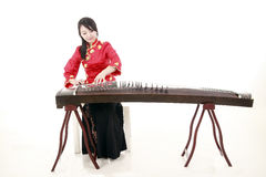 Chinese zither performer. In traditional dress playing zither on white Royalty Free Stock Images