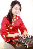 Chinese zither performer. In traditional dress playing zither on white.(close-up Stock Photography