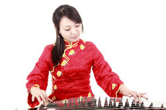 Chinese zither performer. In traditional dress playing zither on white.(close-up Royalty Free Stock Photography
