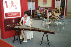 Chinese zitherist at tea exhibition. The young gril in traditional costumes(cheongsam) is playing a chinese zither on The 1st China(Sichuan) International Tea Royalty Free Stock Images