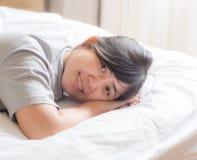 Chinesin, die auf Bett liegt Stockfotos