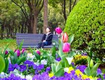 Chinesin, die auf einer Bank sitzt Lizenzfreie Stockfotos