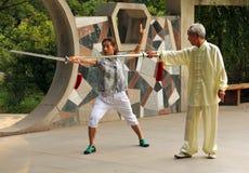 Chinesin, die Form Wushu Jian unter Führung eines Mentors tut Stockbild
