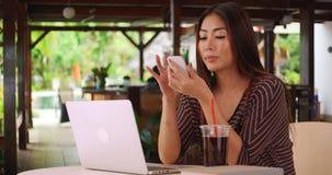 Chinesin, die an ihrem Papier außerhalb des Cafés arbeitet stockfotos