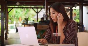 Chinesin, die an ihrem Papier außerhalb des Cafés arbeitet lizenzfreie stockfotos