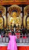 Chinesin, die vor Buddha-Statue betet stockfoto
