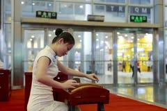 Chinesin, die Zither in der Ausstellung spielt Lizenzfreies Stockbild
