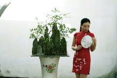 Chinesin im cheongsam in alter Stadt Mudu durch Bäume und Berge eines Bonsais Lizenzfreie Stockfotografie