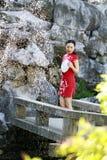 Chinesin im cheongsam durch einen Brunnen in alter Stadt Mudu Stockfotografie