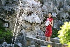 Chinesin im cheongsam durch einen Brunnen in alter Stadt Mudu Lizenzfreie Stockfotos