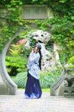 Chinesin in traditionellem blauem und weißem Hanfu-Kleid, das mitten in schönem Tor steht Stockfotografie
