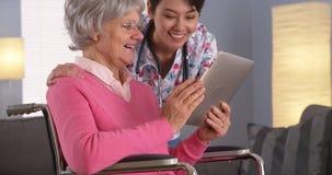 Chinesin und älterer Patient, die mit Tablette sprechen Stockbilder
