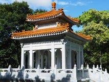 Chinesisch-ähnlicher offener Pavillon unter Vegetation stockfotos