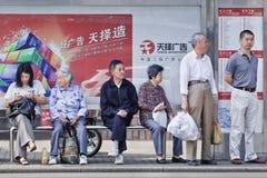 Chinesische ältere Aufwartung an einer Bushaltestelle, Shanghai, China Lizenzfreies Stockbild
