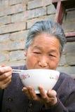 Chinesische alte Frau mit Ess-Stäbchen und Schüssel Stockbilder