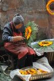 Chinesische alte Frau wand Blumen in eine Girlande stockfotografie