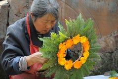 Chinesische alte Frau wand Blumen in eine Girlande. Stockfoto