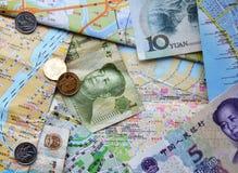Chinesische Banknoten und Münzen auf chinesische Karten Stockfotografie